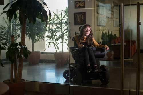 Emily sits among plants in a power wheelchair behind a glass door. She is dimly lit, with long brown hair, a tan turtleneck, and black pants and boots.